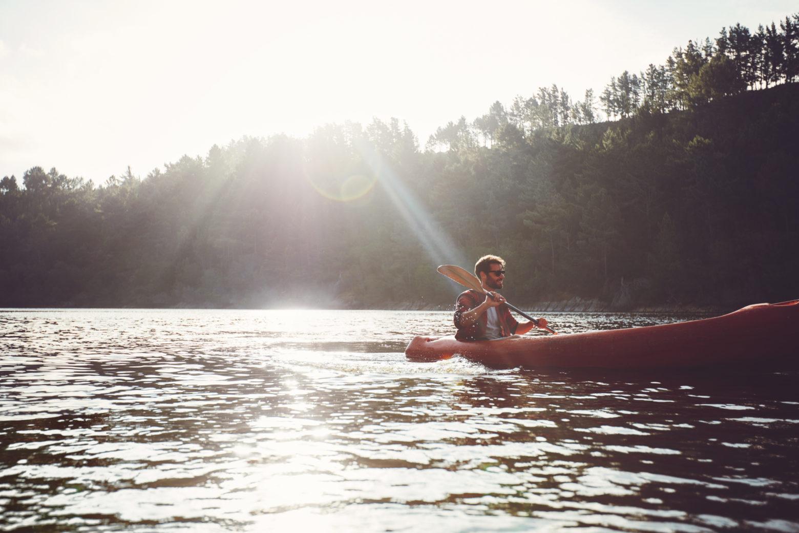Man paddling kayak on a summer day