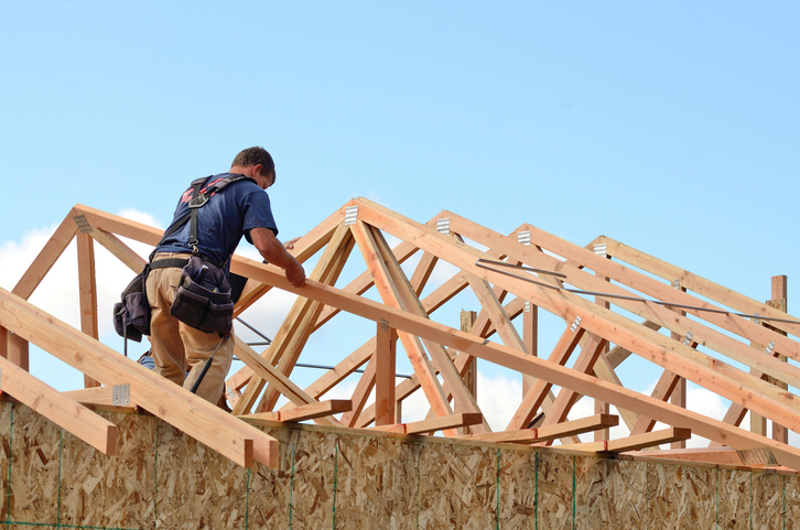 Construction worker piecing together a house frame
